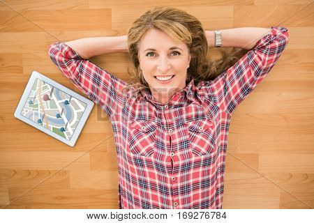 Digitally generated image of navigation pointers against smiling woman lying on floor next to tablet