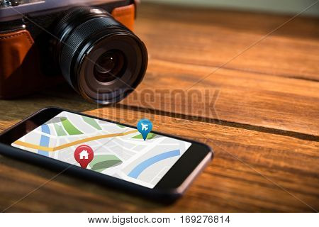 Colorful navigation pointers with various representations on map against smartphone and camera Digital image of colorful navigation pointers with various representations on map