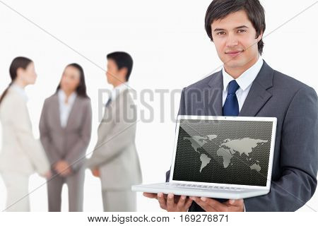 Silver world map over dots against salesman showing laptop screen with colleagues behind him
