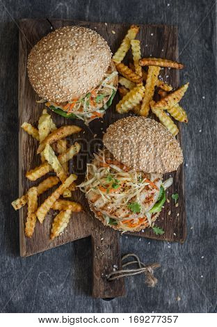 Grilled chicken and coleslaw hamburgers on a wooden board top view
