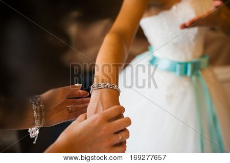 Girl Straightens His Hands Bracelet Jewelry On The Bride's Wrist. Bridesmaid Helps The Bride's Fees