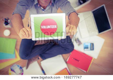 Volunteer against businessman showing tablet computer in creative office