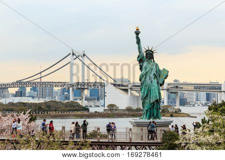 Tokyo Japan - April 8 2016: Lady liberty juxtaposed stand at Odaiba and Rainbow Bridge at Odaiba. Japan.