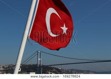 The national flag of Turkey flying in wind, with Bosphorus Bridge at Istanbul in the background.