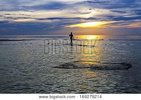 Women silhouette dawn on Thung Wua Lan Beach at Chumphon Province Thailand.