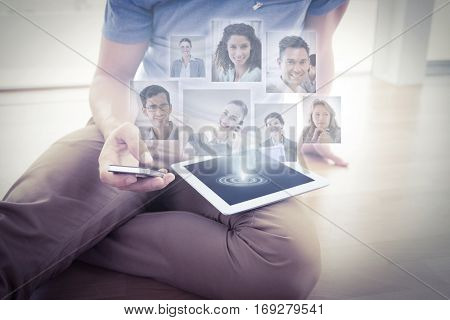 Portrait of business people against businessman sitting on the floor using tablet
