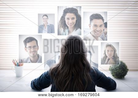 Portrait of business people against young woman typing on computer