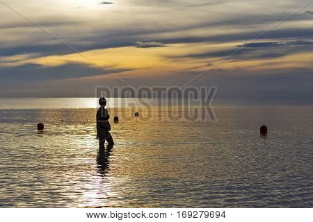 Women shape silhouette sunrise on Thung Wua Lan Beach at Chumphon Province Thailand.