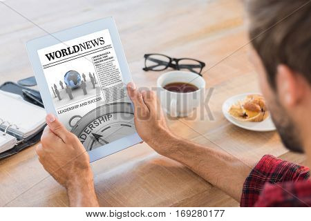 Rear view of man using tablet on wooden table against international newspaper