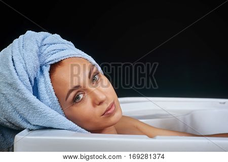 portrait of a girl in a towel on a dark background