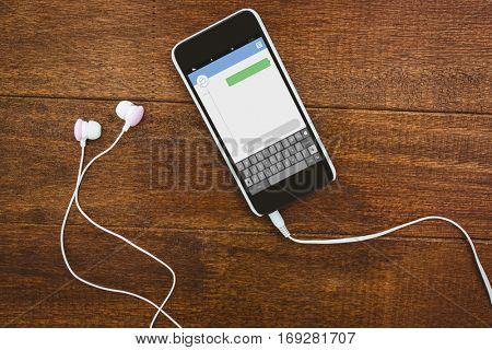 Smartphone text messaging apps against view of a black smartphone with white headphones