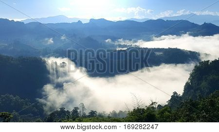 Morning mountain landscape with waves of fog at baan ja bo Mae Hong Son Northern Thailand. Waves of clouds in the background peaks covered with coniferous deciduous forests