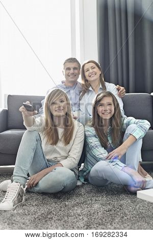 Happy family of four watching TV together at home