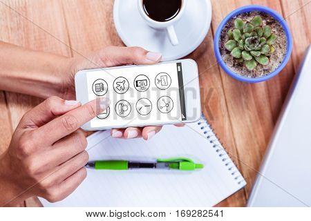 Telephone apps icons against overhead of feminine hands using smartphone