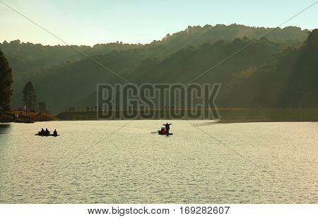 Tourist sitting and standing on the bamboo raft floating in clear water in the morning at Pang Oung Lake (Pang Tong reservoir) Mae hong son Thailand.