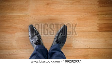 Businessman standing isolated on white background against wooden flooring