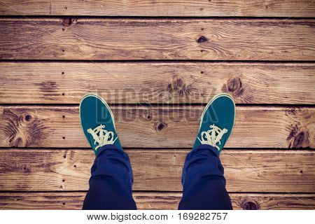 Man with canvas shoes on hardwood floor against wooden planks background