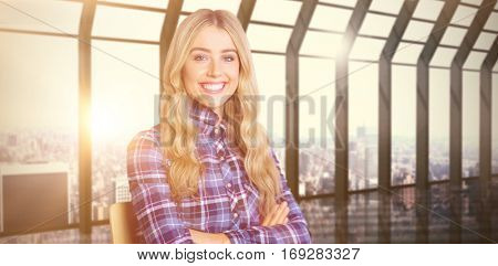 Pretty casual worker smiling at camera against room with large window looking on city