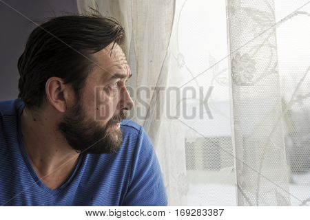 Pensive man looking through the window