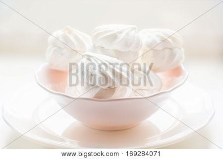 Marshmallows in pink plate on a white background.
