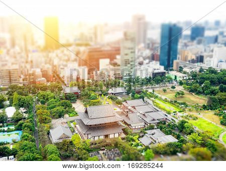 Business and culture concept - panoramic modern city skyline bird eye aerial view with zojo-ji temple shrine from tokyo tower under dramatic sunrise and morning blue sky in Tokyo Japan. Miniature Tilt-shift effect