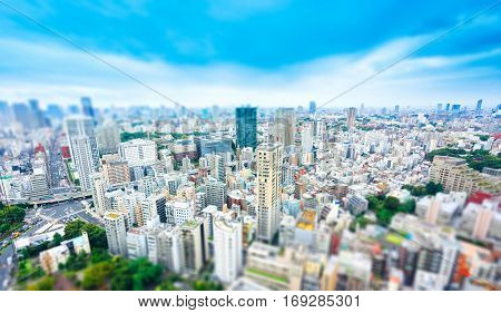 Business and culture concept - panoramic modern city skyline bird eye aerial view from tokyo tower under dramatic sunny and morning blue cloudy sky in Tokyo Japan. Miniature Tilt-shift effect