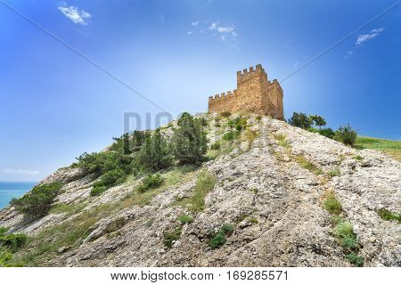 Genoese fortress view from below the bright daytime photo fortress on a background of blue sky
