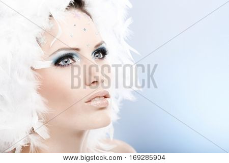 Portrait of mystical winter beauty with strasses and white feather hat.