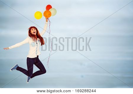 Smiling hipster woman holding balloons against bleached wooden planks background