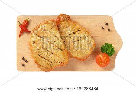 Two grilled honey glazed pork chops on cutting board