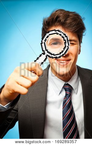 young man in business suit is looking through a digital loupe