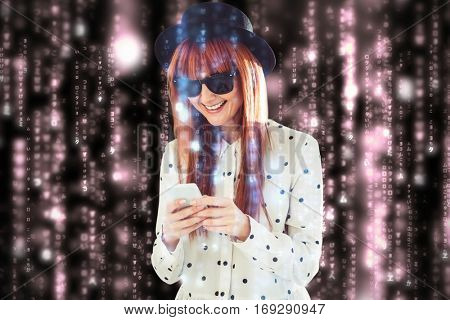 Smiling hipster woman texting with her smartphone against lines of orange blurred letters falling
