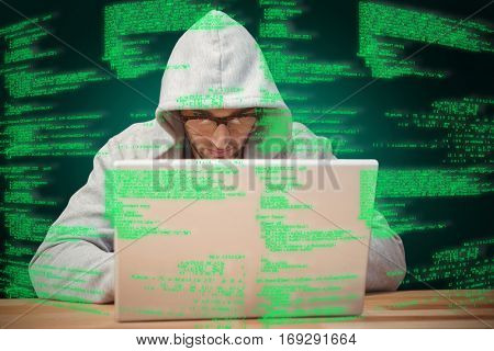 Creative businessman with hooded shirt working on laptop against green background with vignette