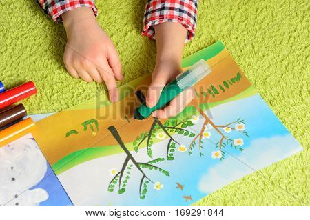 the child draws a picture lying on a green carpet