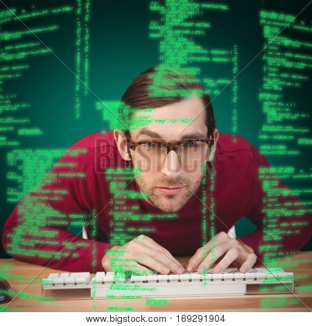 Portrait of concentrated man working on computer against green background with vignette