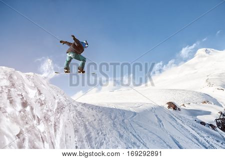 Stylish snowboarder with helmet and mask jumps from high snow slope against the blue sky and the extinct volcano Elbrus