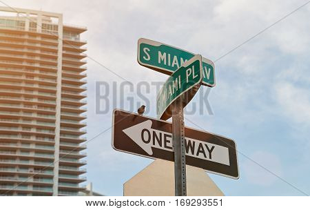 Miami city street sign on skyscraper sky background. Sign arrows of miami street