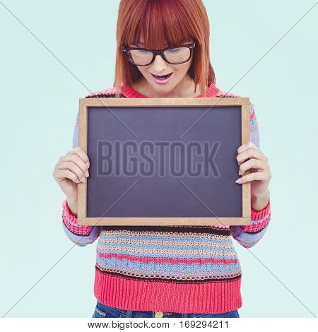 Smiling hipster woman holding blackboard against blue background
