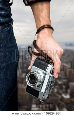 Hipster man holding digital camera against new york