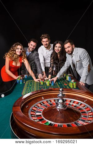 Group of young people behind roulette table on black background. young people are betting in the game. Looking at the camera