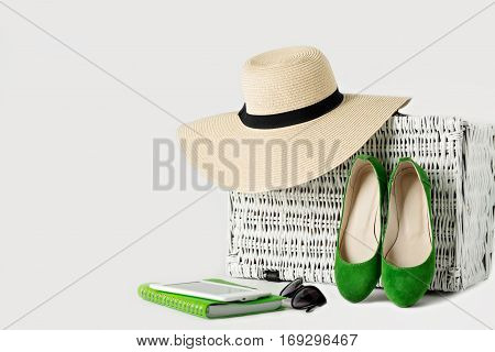 White wicker suitcase womens hat sunglasses green shoes e-book and notepad. Selective focus.