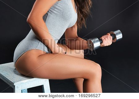 Fitness-instructor in sports clothing on black background. Female model with fit muscular and slim body in sportswear. Young fit woman lifting dumbbells
