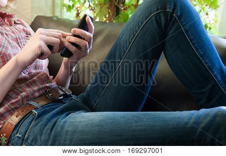 mid adult woman relaxing on sofa and browsing on smartphone