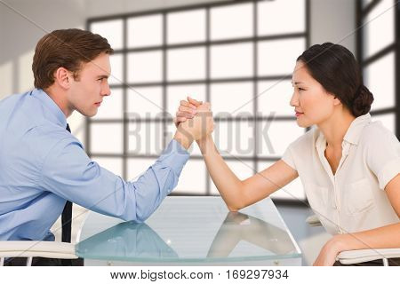 Business couple arm wrestling at desk against room with a lot of windows