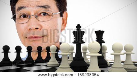 Close-up portrait of confident man wearing eyeglasses against black king and queen surrounded by white pawns
