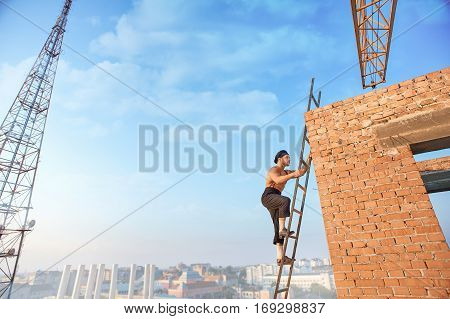 Side view of handsome builder with bare torso in hat climb up ladder up. Ladder leaning on brick wall at un finished building. High TV tower and cityscape on background.
