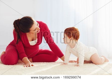 Happy Pregnant Mother And Toddler Baby Playing At Home