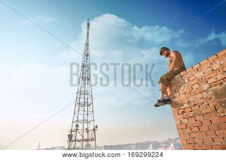 Back view of muscular builder in work wear standing on brick wall on high. Man holding hands in pockets and looking down. Extreme in hot summer day. Blue sky and high TV tower on background.