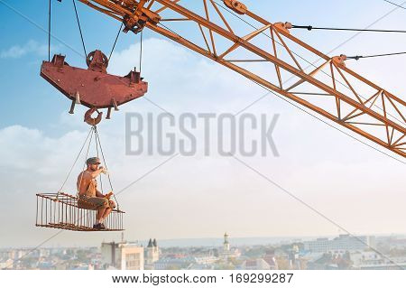 Builder with bare torso sitting on iron construction on high eating and drinking milk. Crane holding construction. Male wearing work wear. Extreme building. Blue sky and cityscape on background.