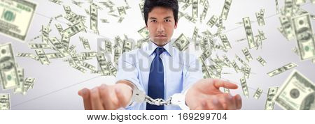 Businessman with handcuffs against dollars falling